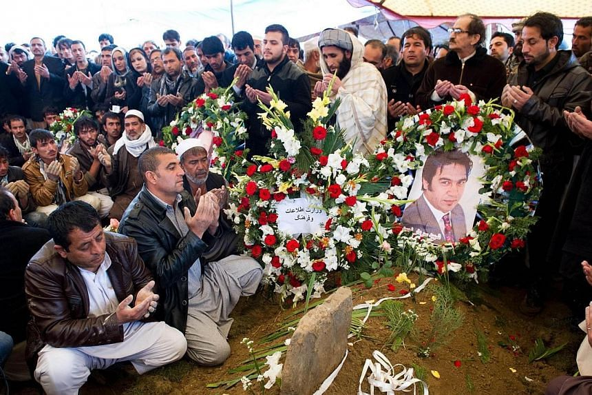 Friends and family of Afghan AFP reporter Sardar Ahmad pray over his grave during his funeral in Kabul on March 23, 2014. -- PHOTO: AFP
