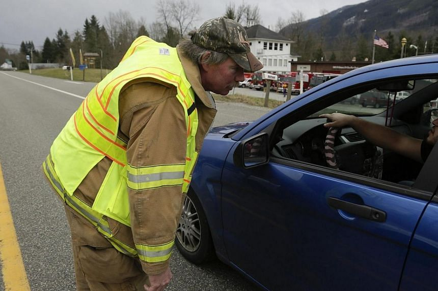 An emergency worker instructs vehicles to turn around after a large mudslide blocked Highway 530 near Oso, Washington on March 22, 2014. -- PHOTO: REUTERS