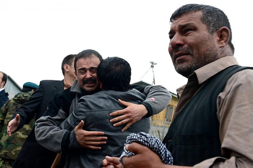Mr Eeraj (centre), the nephew of slain Afghan AFP reporter Sardar Ahmad, mourns his passing during funeral ceremonies in Kabul on March 23, 2014. -- PHOTO: AFP