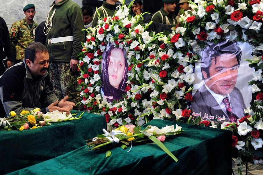 Mr Eeraj (left), the nephew of slain Afghan AFP reporter Sardar Ahmad laments over the coffins of two of Sardar's children alongside images of Sardar's wife Homaira (centre) and Sardar (right) during funeral ceremonies in Kabul on March 23, 2014. --
