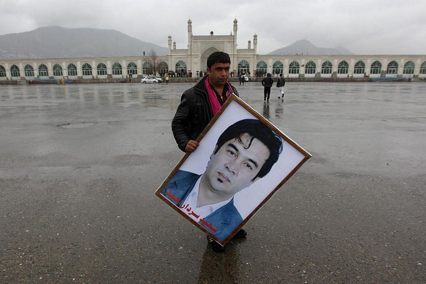 An Afghan man holds a picture of Afghan journalist Sardar Ahmad of Agence France-Presse, during his funeral ceremony in Kabul on March 23, 2014. -- PHOTO: AFP