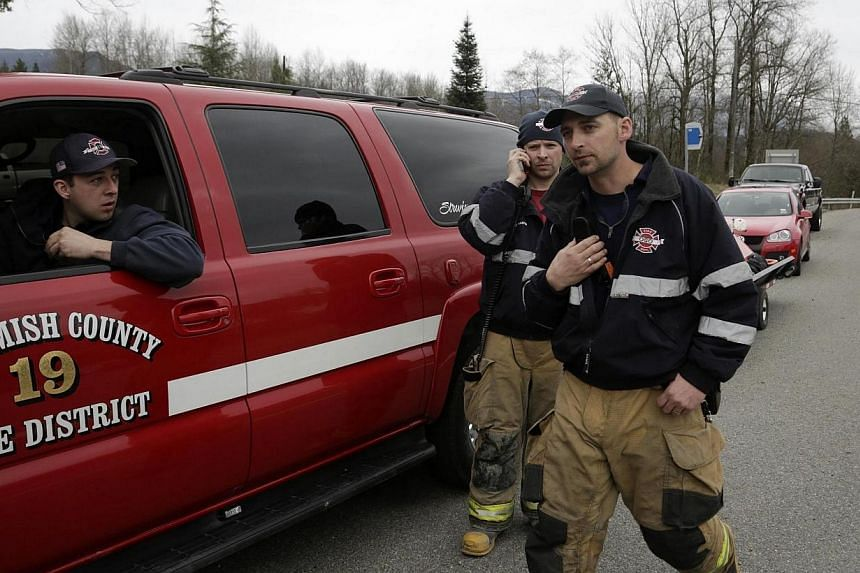 Members of a swift water rescue team monitor radio traffic after a large mudslide blocked Highway 530 near Oso, Washington on March 22, 2014. -- PHOTO: REUTERS
