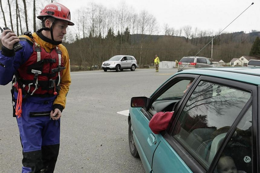 An emergency worker instructs a resident and his family to evacuate after a large mudslide blocked Highway 530 near Oso, Washington on March 22, 2014. -- PHOTO: REUTERS