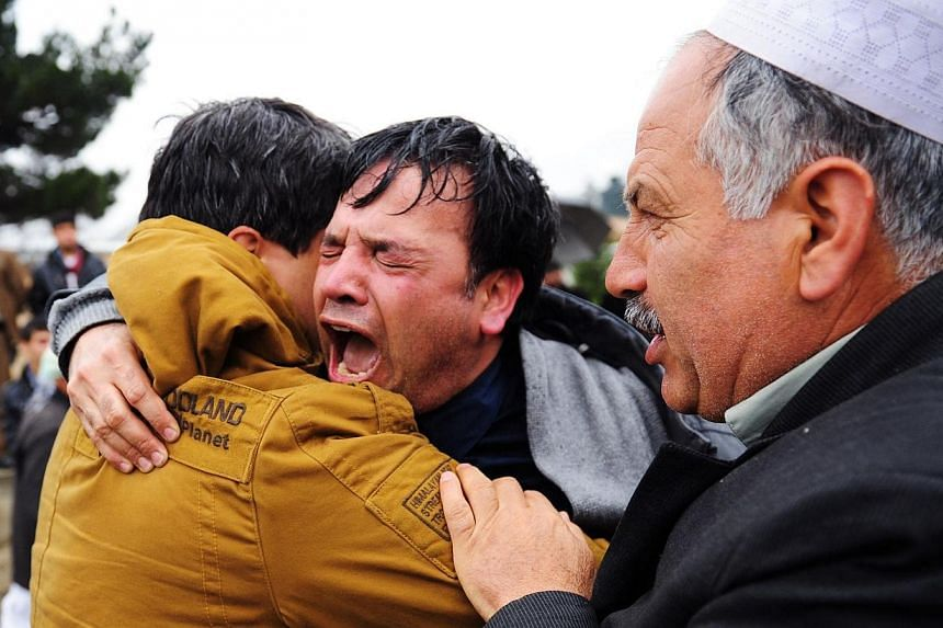 Mr Bashad (centre), a brother of Afghan AFP reporter Sardar Ahmad, mourns his brother's passing during the funeral ceremonies in Kabul on March 23, 2014. -- PHOTO: AFP