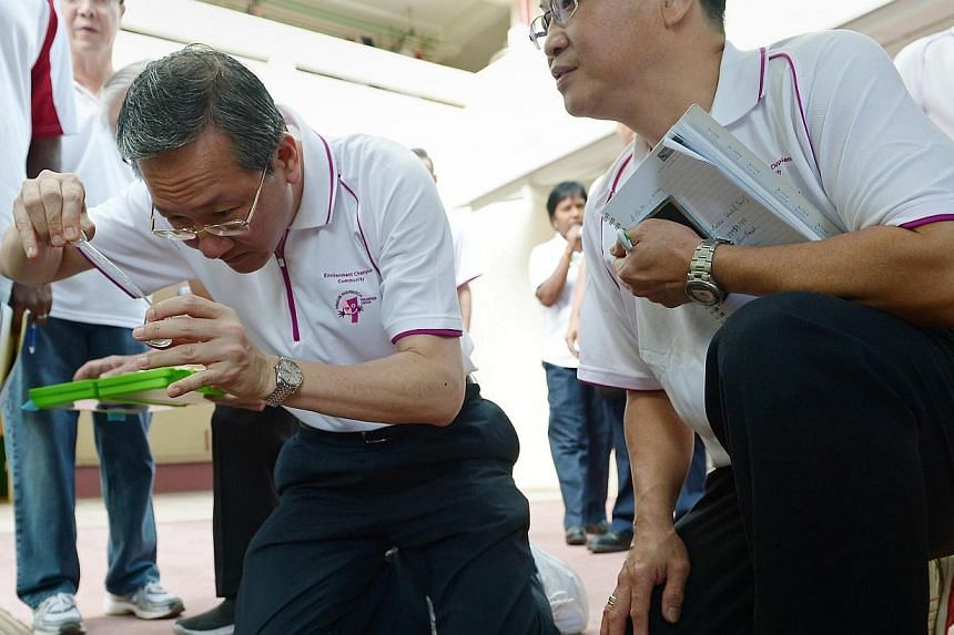 Grassroots Advisor Sam Tan Chin Siong, Mayor of Central Singapore District and MP for Radin Mas SMC checks a drain at Telok Blangah Crescent for the dengue mosquitoes. Residents in three blocks at Telok Blangah Crescent got a refresher course on how