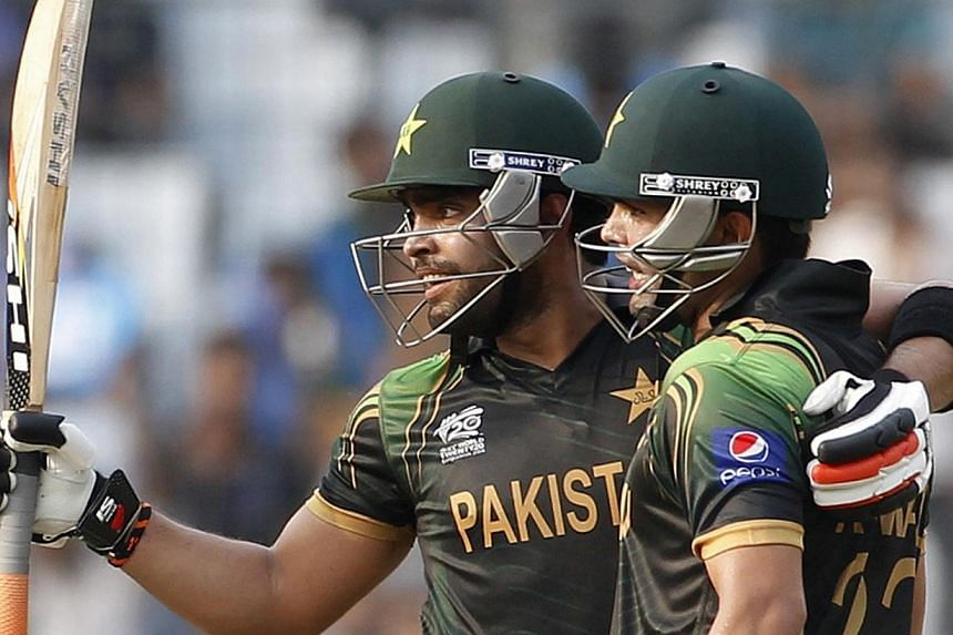 Pakistan's Umar Akmal celebrates after scoring a half century as teammate Kamran Akmal (right) congratulates him during their ICC Twenty20 World Cup match against Australia at the Sher-E-Bangla National Cricket Stadium in Dhaka on March 23, 2014.&nbs