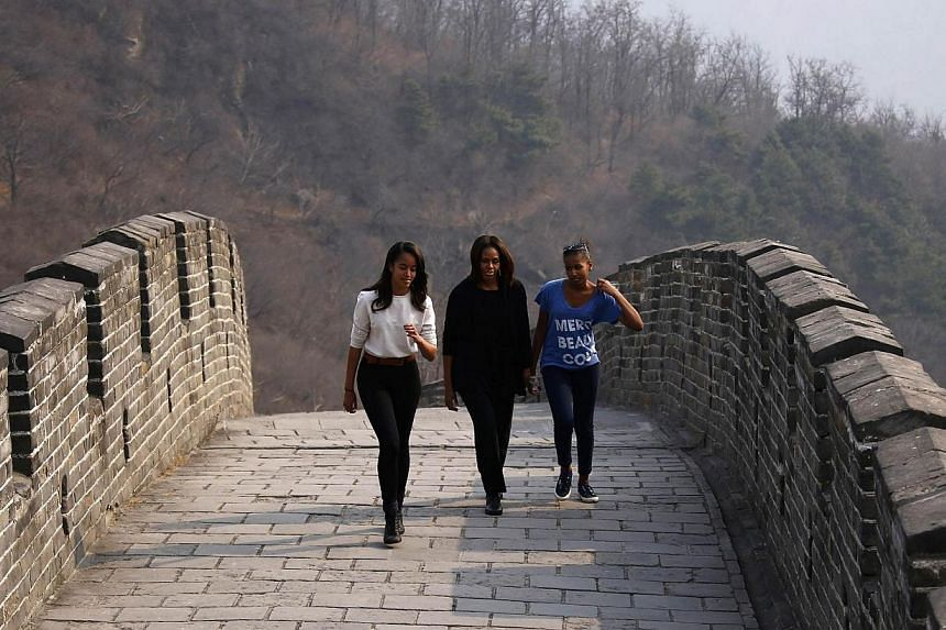 U.S. first lady Michelle Obama (centre) walks with her daughters Sasha (right) and Malia as they visit the Mutianyu section of the Great Wall of China, in Beijing March 23, 2014. Visiting US first lady Michelle Obama held a meeting on Sunday, March 2