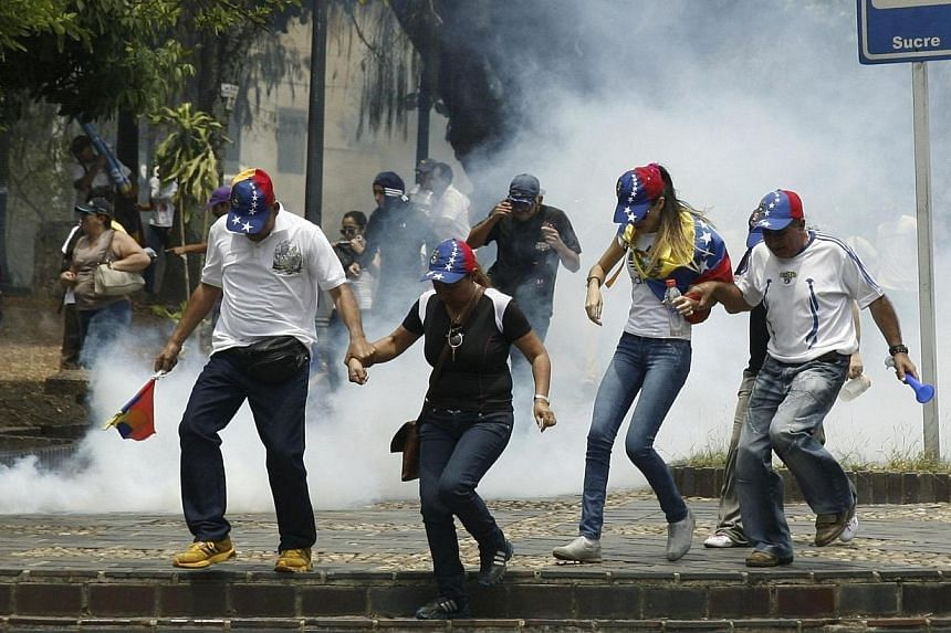 Anti-government protesters run from tear gas during a protest against Nicolas Maduro's government in San Cristobal March 22, 2014. Police fired tear gas and made several arrests as 20,000 people marched Saturday, March 23, 2014, in the Venezuela