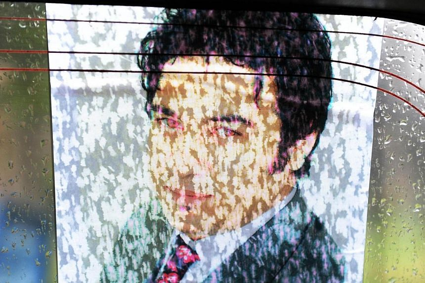 Drops of rain disolve ink on a printout bearing the image of Afghan AFP reporter Sardar Ahmad afixed to a window of a car during a convoy at his funeral in Kabul on March 23, 2014. -- PHOTO: AFP