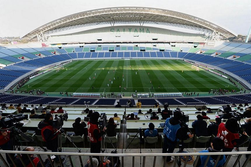 Journalists and cameramen sit in the press tribune overlooking an empty Saitama 2002 Stadium where the Urawa Red Diamonds are playing against the Shimizu S-Pulse in their J-League football match in Saitama on March 23, 2014. Japan's best-supported cl