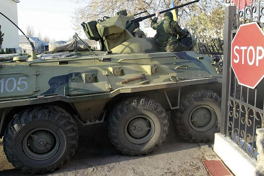 Armed men, believed to be Russian servicemen, drive an armoured vehicle onto the territory of a military airbase as they attempt to take over in the Crimean town of Belbek near Sevastopol March 22, 2014. Kiev braced for a unity rally on Sunday, March
