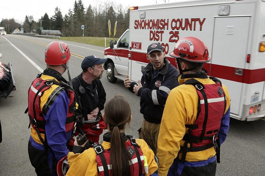 Members of a swift water rescue team huddle as an ambulance heads in the direction of a large mudslide that has blocked Highway 530 near Oso, Washington on March 22, 2014. -- PHOTO: REUTERS