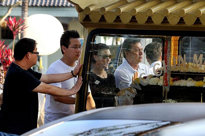 Mr Victor Lim (centre, in white) and sister Sharon Lim beside him (in black) sending the funeral car off. Ms Nancy Gan - artist, socialite and philanthropist - was cremated on Sunday evening at Mandai Crematorium and Columbarium, after a tw