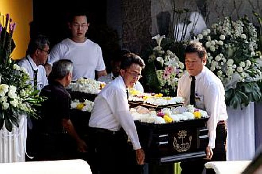 Mr Victor Lim (centre, in white) followed closely as his mother's casket was carried out of the funeral parlour.-- ST PHOTO:LAU FOOK KONG