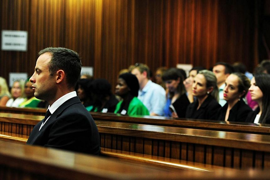 South African Paralympic athlete Oscar Pistorius (left) sits in the docks on the 13th day of his trial for the murder of his girlfriend Reeva Steenkamp at the North Gauteng High Court in Pretoria on March 19, 2014. -- FILE PHOTO: AFP
