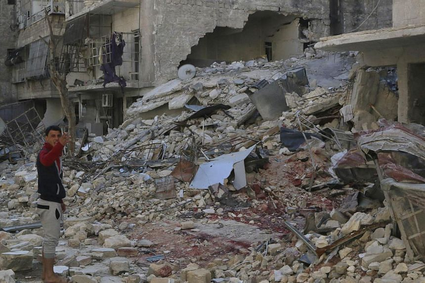 A man stands on the debris of damaged buildings in al-Katerji district in Aleppo on March 22, 2014. Syrian rebels seized a strategic hill west of Aleppo after a fierce battle with government troops on Saturday as fighting elsewhere in the north sprea