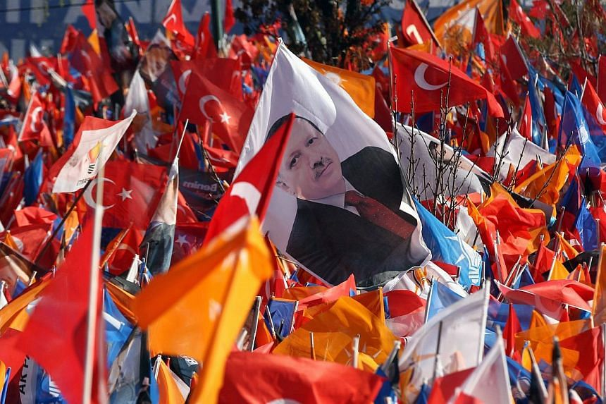 Supporters of Turkey's prime minister wave Turkish and the ruling Justice and Development Party (AKP) flags during an election rally in Ankara on March 22, 2014. -- PHOTO: AFP