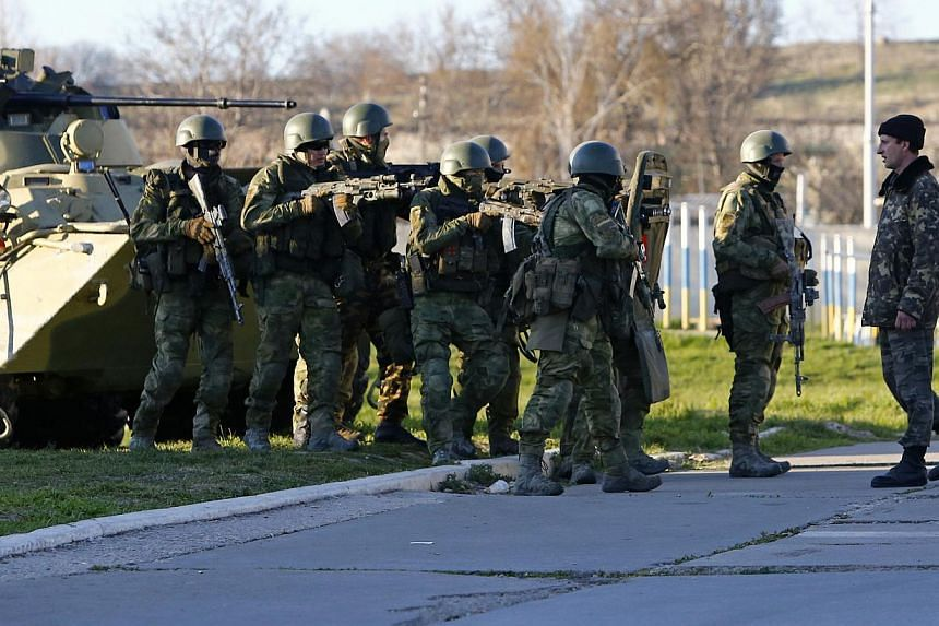 A Ukrainian serviceman (right) talking to armed men, believed to be Russian servicemen, who stand guard at a military airbase, in the Crimean town of Belbek near Sevastopol on March 22, 2014. -- PHOTO: REUTERS