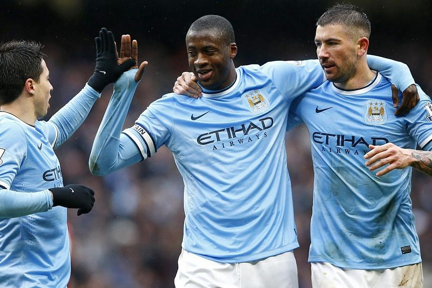 Manchester City's Yaya Toure (centre) celebrating with team mates Samir Nasri (left) and Aleksandar Kolarov after scoring a third goal against Fulham during their English Premier League match at the Etihad stadium on March 22, 2014. -- PHOTO: REUTERS