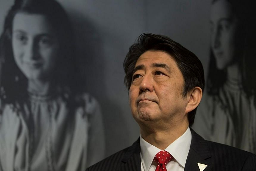 Japan's Prime Minister Shinzo Abe visits the Anne Frank House in Amsterdam on March 23, 2014. Mr Abe was visiting the Anne Frank House museum in Amsterdam on Sunday to highlight Japan's friendship with the Jewish people and sees no contradiction with
