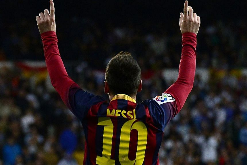 Barcelona's Argentinian forward Lionel Messi celebrates after scoring during the Spanish league Clasico football match against Real Madrid at the Santiago Bernabeu on March 23, 2014. -- PHOTO: AFP