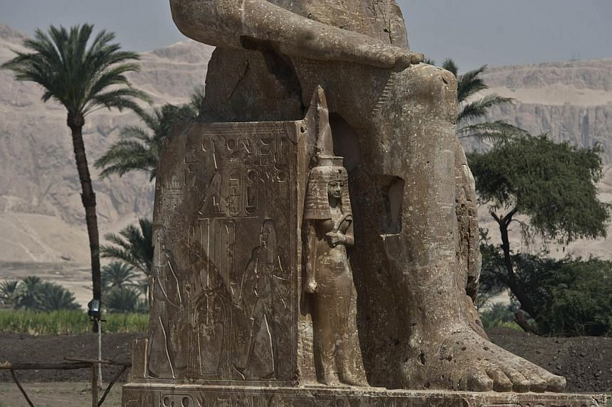 A part of a newly displayed statue of pharaoh Amenhotep III and his wife Tiye (down) in Egypt's temple city of Luxor on March 23, 2014. -- PHOTO: AFP