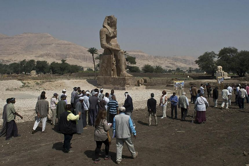 Tourists and journalists walk past a newly displayed statue of pharaoh Amenhotep III in Egypt's temple city of Luxor on March 23, 2014. -- PHOTO: AFP