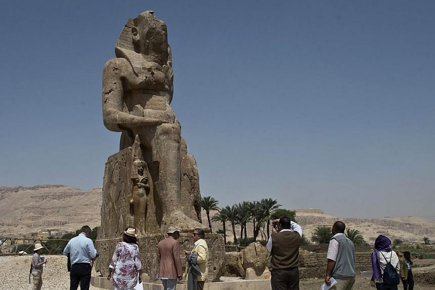 Tourists and journalists stand next to a newly displayed statue of pharaoh Amenhotep III and his wife Tiye (down) in Egypt's temple city of Luxor on March 23, 2014. -- PHOTO: AFP