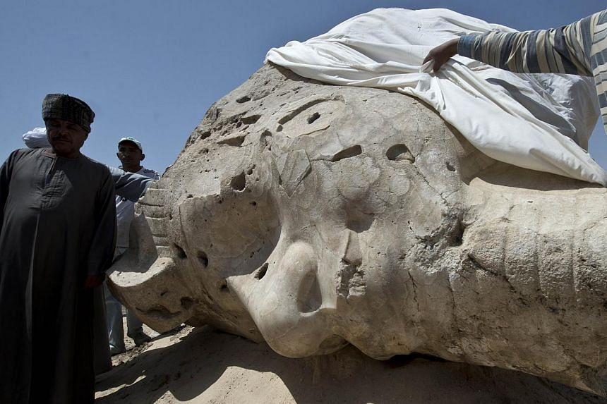 Egyptian archaeological workers stand next to a newly displayed alabaster head from an Amenhotep III statue in Egypt's temple city of Luxor on March 23, 2014. -- PHOTO: AFP