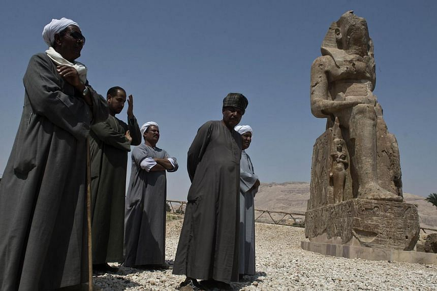 Egyptian archaeological workers stand next to a newly displayed statue of pharaoh Amenhotep III in Egypt's temple city of Luxor on March 23, 2014. -- PHOTO: AFP