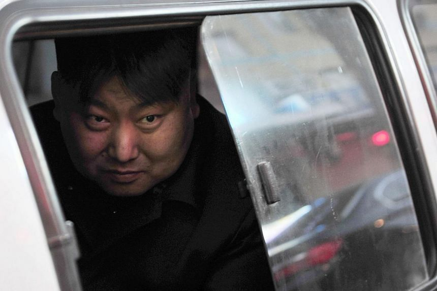 Xia, a 38-year-old lookalike of North Korean leader Kim Jong Un, looks out from a vehicle near his barbeque food stall in Shenyang, Liaoning province, on March 22, 2014. Street vendor Xia and his food stall in the northern city Shenyang went viral af
