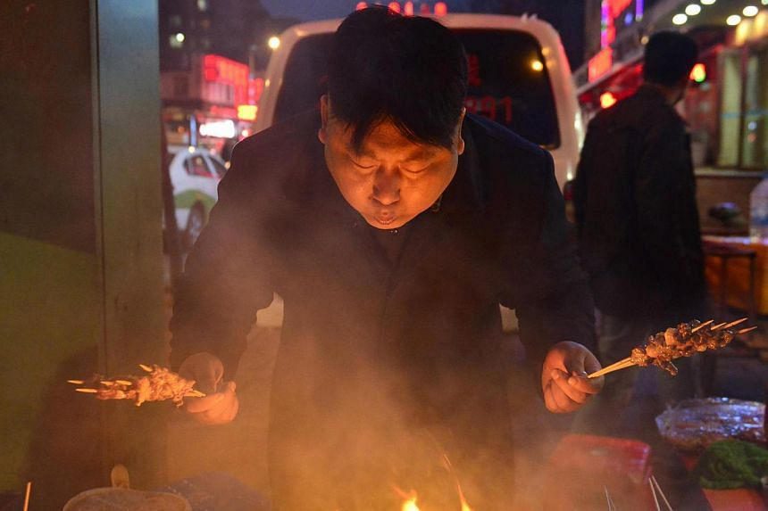 Xia, a 38-year-old lookalike of North Korean leader Kim Jong Un, cooks barbequed lamb at his food stall in Shenyang, Liaoning province, on March 22, 2014. Street vendor Xia and his food stall in the northern city Shenyang went viral after pictures of