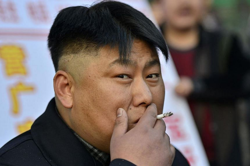 Xia, a 38-year-old lookalike of North Korean leader Kim Jong Un, smokes a cigarette at his barbeque food stall in Shenyang, Liaoning province, on March 22, 2014. Street vendor Xia and his food stall in northern city Shenyang went viral after pictures