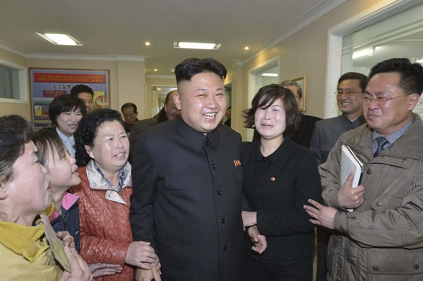 North Korean leader Kim Jong Un (C) strikes fear into some hearts, but photos of a Chinese street food vendor known only as Xia with a distinct resemblance to the Pyongyang strongman have fuelled online mirth.-- FILE PHOTO: REUTERS
