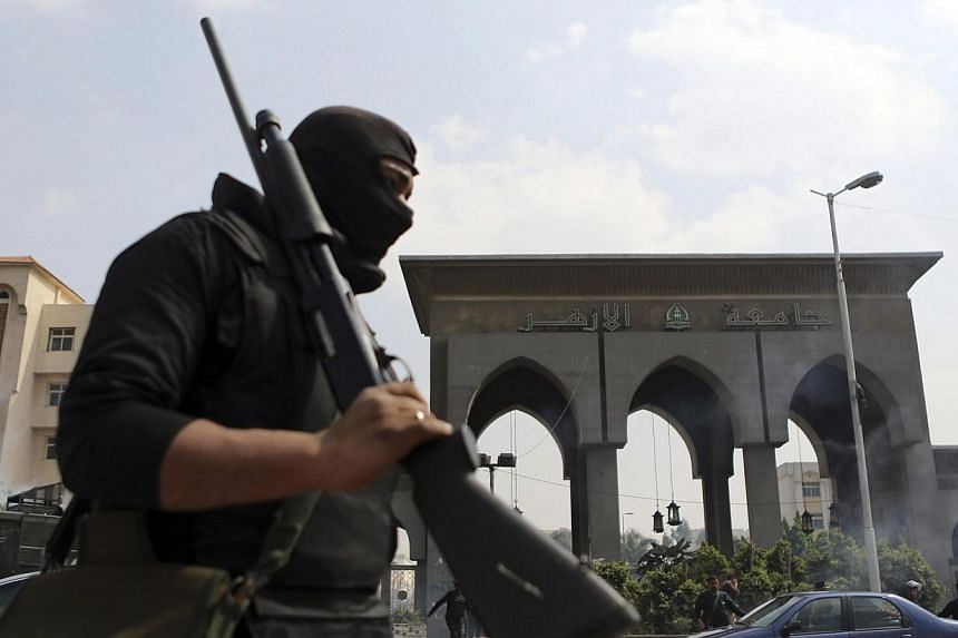 A riot police holds his weapon during clashes with al-Azhar University students, who are supporting the Muslim Brotherhood and deposed President Mohamed Mursi, on the university campus in Cairo's Nasr City district, March 19, 2014. A court in Egypt o