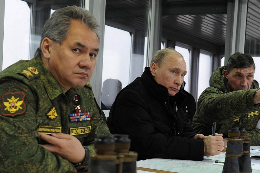Russia's President Vladimir Putin (centre) listens to the head of the Russian army's main department of combat preparation Ivan Buvaltsev (tight) while watching military exercises at the Kirillovsky firing ground in the Leningrad region, on March 3,