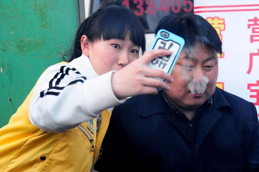 A girl (left) takes a selfie with a Chinese street food vendor with a resemblance to North Korean leader Kim Jong Un as he sits by his barbecue stall in Shenyang, north-east China's Liaoning province, on March 22, 2014. -- FILE PHOTO: AFP