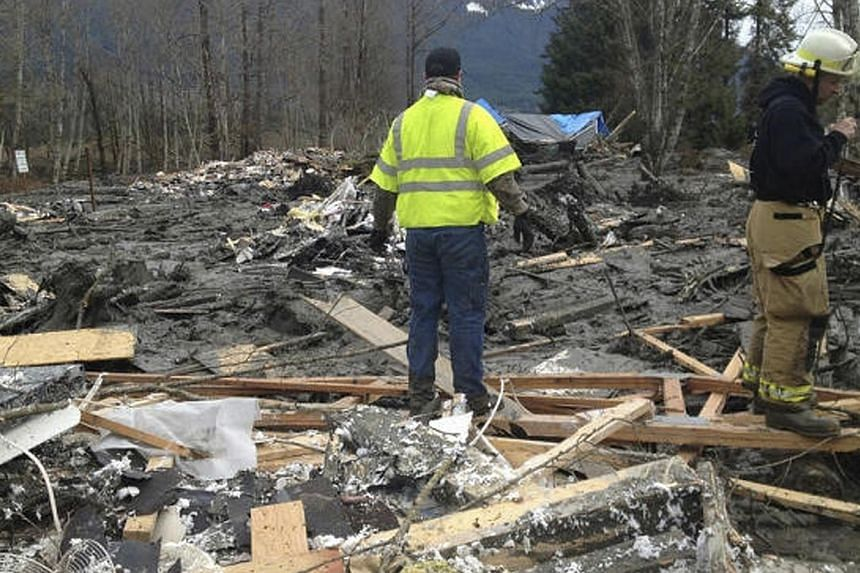 Officials survey a large mudslide in this handout photo provided by the Washington State Police near Oso, Washington, on March 22, 2014. -- PHOTO: REUTERS/WASHINGTON STATE DEPARTMENT OF TRANSPORTATION