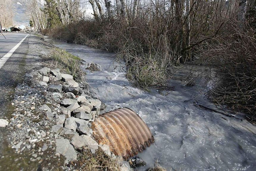 Water flows into a ditch as a landslide blocks Highway 530 near Oso, Washington, on March 23, 2014. -- PHOTO: REUTERS