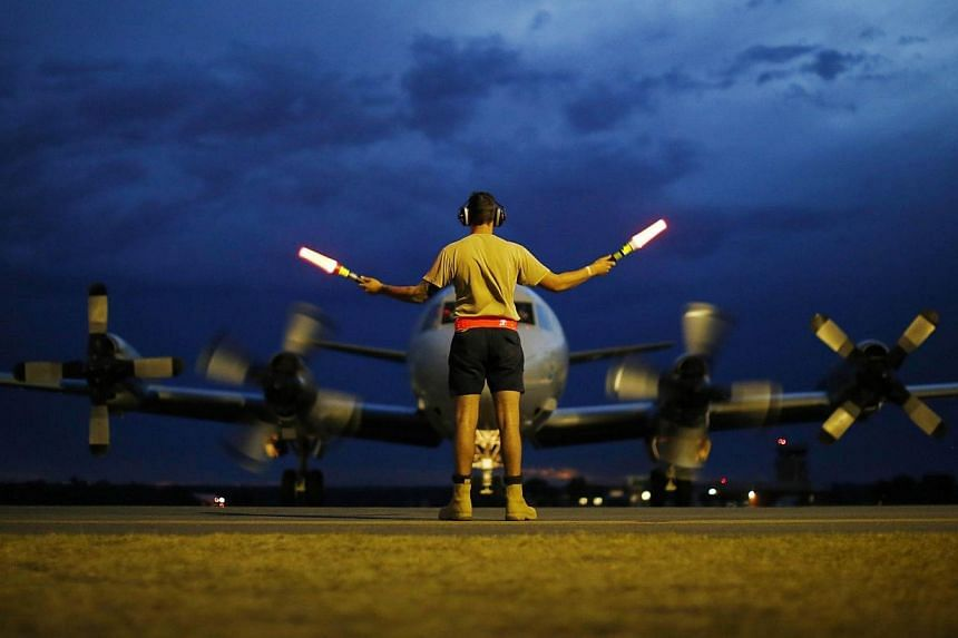 A ground controller guides a Royal Australian Air Force AP-3C Orion to rest after sunset upon its return from a search operation for the missing Malaysia Airlines flight MH370 over the Indian Ocean, at Pearce Airbase in Bullsbrook, 35kms north of Per