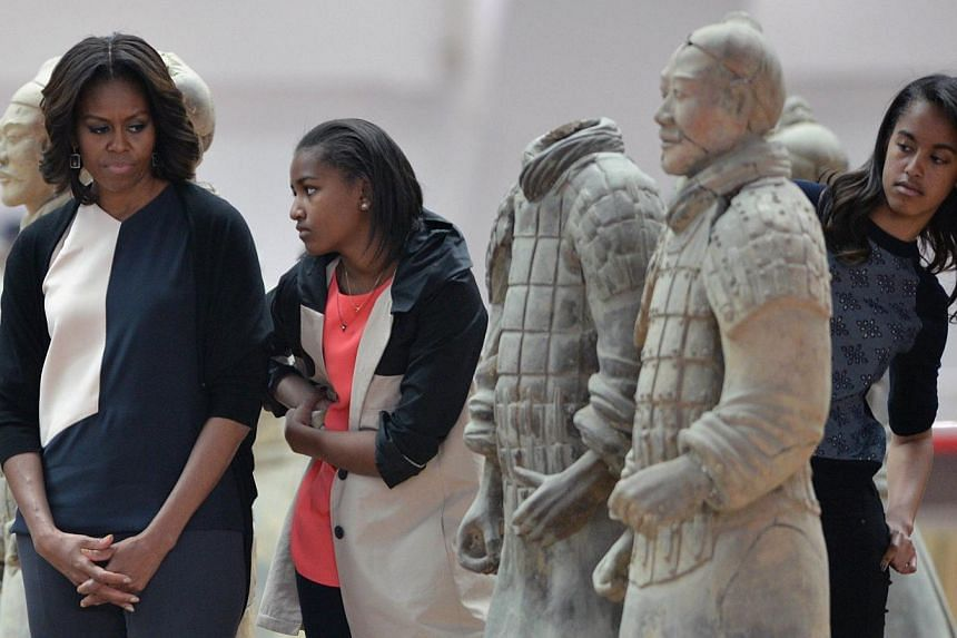 US First Lady Michelle Obama (left) and daughters Sasha (centre) and Malia (right) look at the Terracotta Warriors in China's central Shaanxi province of Xian on March 24, 2014.-- PHOTO: AFP