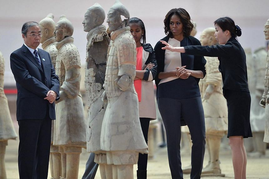 US First Lady Michelle Obama (centre right) and daughter Sasha (centre) look at the Terracotta Warriors in China's central Shaanxi province of Xian on March 24, 2014.-- PHOTO: AFP