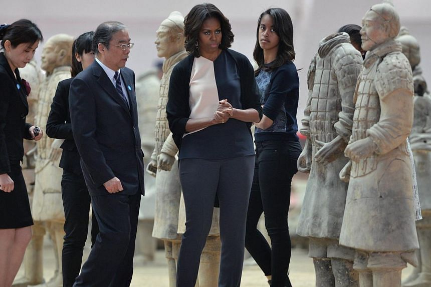 US First Lady Michelle Obama (centre) and daughter Sasha Maila (centre right) look at the Terracotta Warriors in China's central Shaanxi province of Xian on March 24, 2014.-- PHOTO: AFP