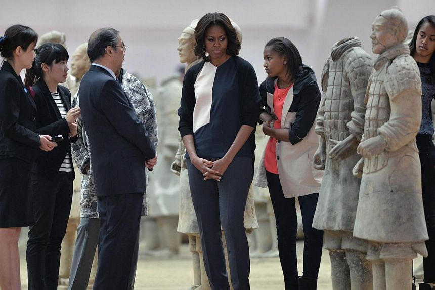 US First Lady Michelle Obama (centre) and daughters Sasha (centre right) and Maila (right) look at the Terracotta Warriors in China's central Shaanxi province of Xian on March 24, 2014.-- PHOTO: AFP