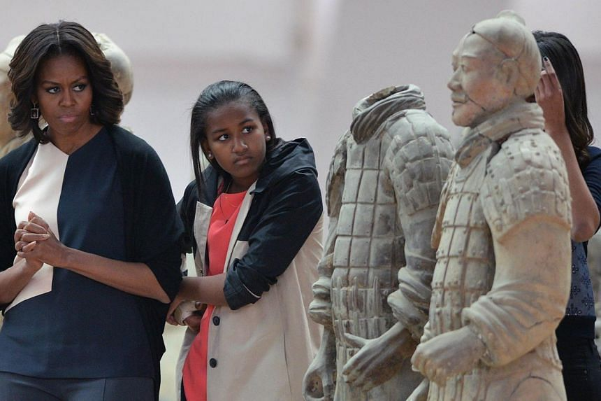 US First Lady Michelle Obama (left) and daughters Sasha (centre) and Maila (right) look at the Terracotta Warriors in China's central Shaanxi province of Xian on March 24, 2014. -- PHOTO: AFP