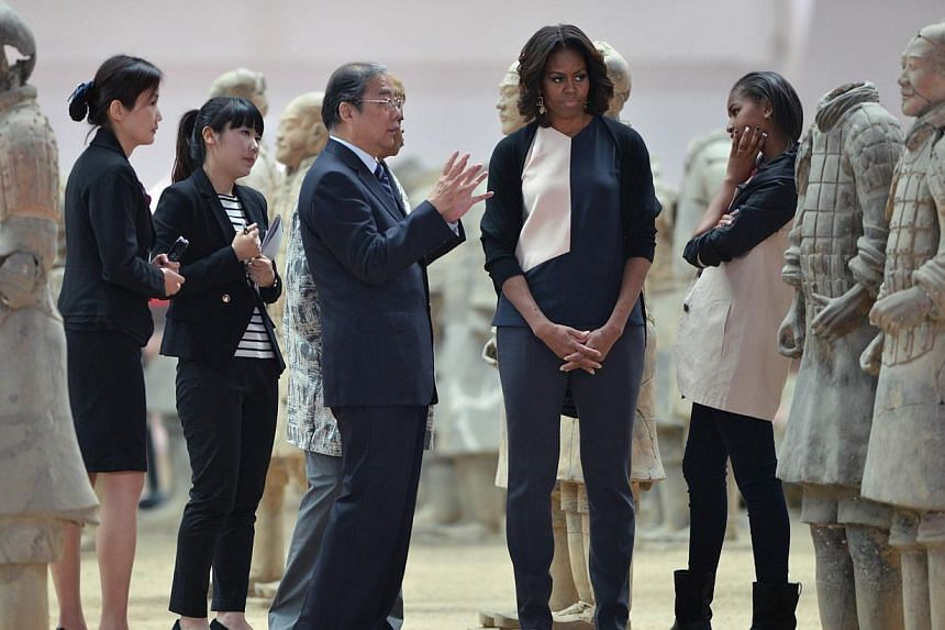 US First Lady Michelle Obama (centre) and daughters Sasha (centre right) and Malia (right) look at the Terracotta Warriors in China's central Shaanxi province of Xian on March 24, 2014.Visiting US First Lady Michelle Obama, along with her daugh