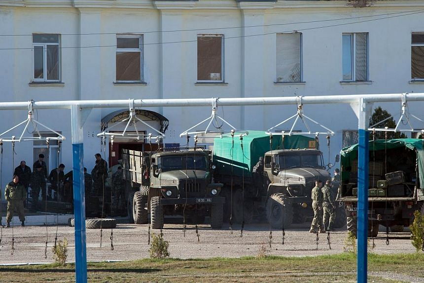 Ukrainian soldiers load weapons and amunition into trucks at the Ukrainian marine battalion in the Crimean city of Feodosia on March 23, 2014. Russian troops on Monday, March 24, 2014, seized control of a new Ukrainian military base in Crimea, t