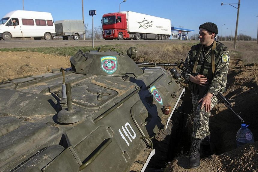 A Ukrainian serviceman stands on guard at a checkpoint near the town of Armyansk in Kherson region adjacent to Crimea, March 23, 2014. Ukraine's acting president announced on Monday, March 24, 2014, that the ex-Soviet nation's troops have been g