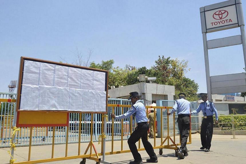 Private security guards move a barricade outside a closed plant of Toyota Motor Corp's India unit near Bangalore on March 18, 2014.Employees at Toyota's auto assembly plants in southern India failed to return to work on Monday, March 24, 2014,
