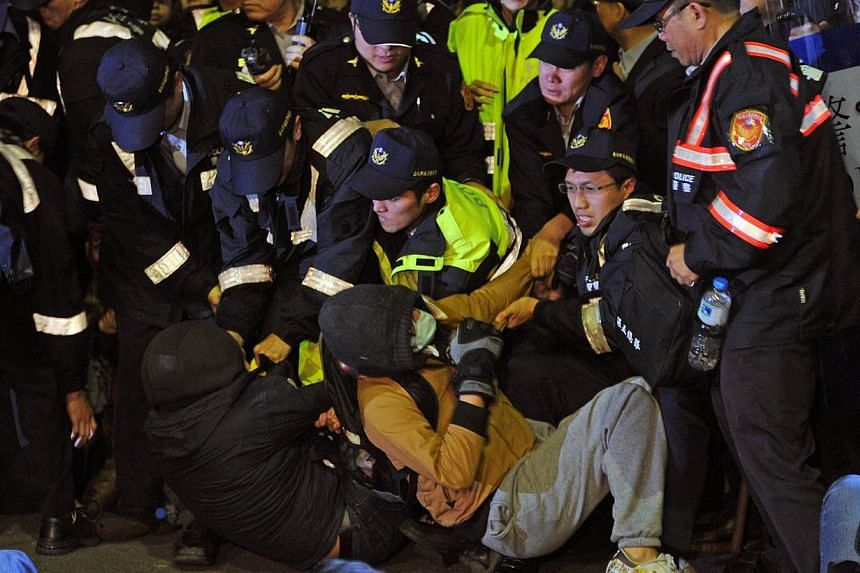 Police remove students from the ground at the Excutive Yuan in Taipei on early March 24, 2014. -- PHOTO: AFP